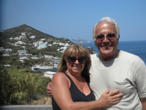 Ralph De Falco con la moglie sullo fondo di Cala Feola