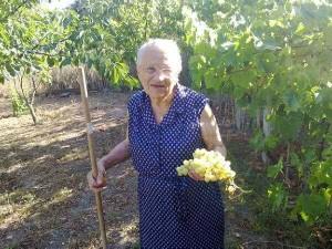 Zia Elia con una pigna d'uva del suo giardino