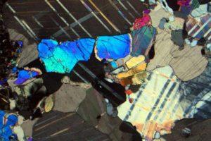 cristalli-di-niocalite-alti-colori-di-interferenza-cristalli-di-apatite-grigio-i-ordine-e-calcite-in-una-carbonatite-plutonica-sovite-di-oka-quebec-canada
